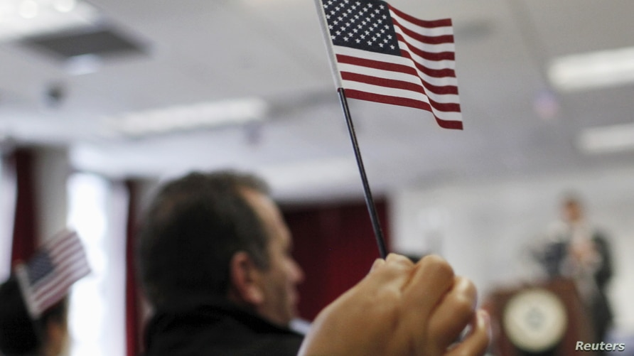 A new U.S. citizen waves a U.S. flag after taking the Oath of Allegiance during a special naturalization ceremony at the U.S…