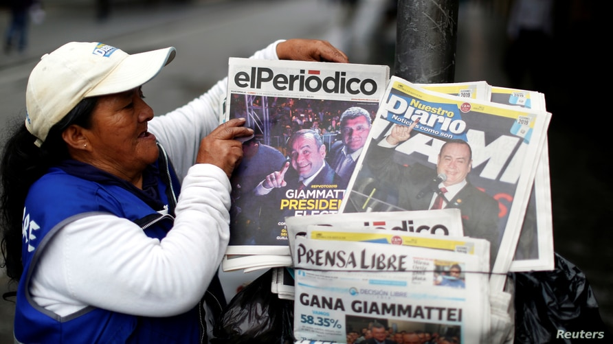 A woman sells newspapers with pictures of presidential candidate Alejandro Giammattei, the winner of the presidential election,…