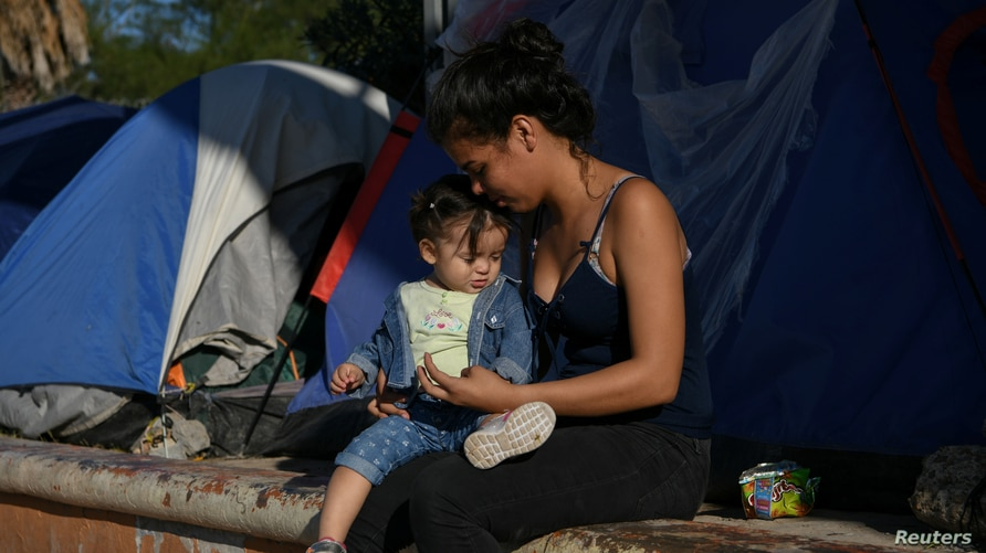Central American migrants pass the time at a makeshift encampment occupied by asylum seekers sent back to Mexico from the U.S…