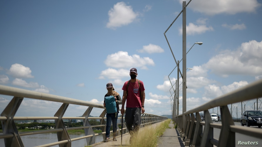 Two Venezuelan immigrants cross the National Unity Bridge on their way to Peru where family members can take them in, amid the…