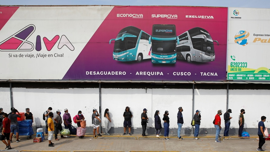 People are standing in line outside a bus terminal as Peru's capital Lima, and nine other regions, start a total lockdown at…