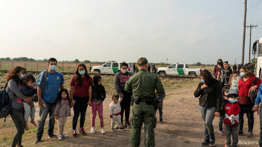 Asylum-seeking migrant families wait to be transported by the U.S. Border Patrol after crossing the Rio Grande river into the…