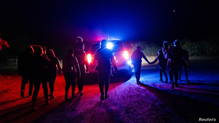 Asylum-seeking migrant families walk while being escorted by the U.S. Border Patrol after crossing the Rio Grande river into…