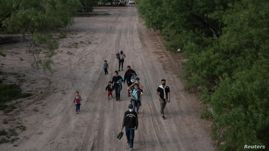 Asylum seeking migrants from Central America walk north along a dirt road after crossing the Rio Grande river into the United…