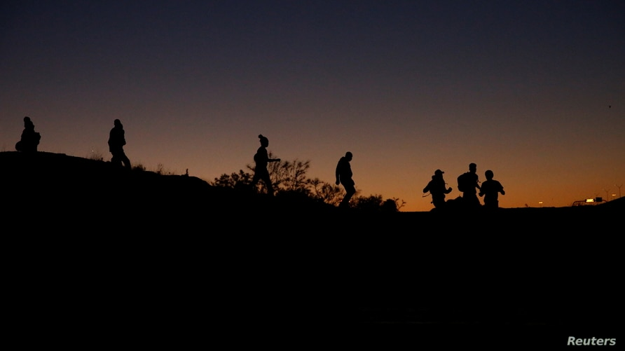 Asylum-seeking migrants are seen before crossing the Rio Bravo river to turn themselves in to U.S Border Patrol agents to…