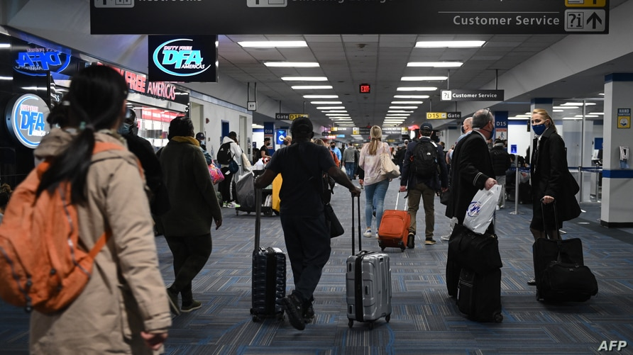 Passengers walk through a crowded terminal at Dulles International airport in Dulles, Virginia on December 27, 2020 amid the…