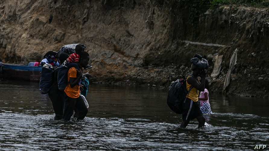 Migrants cross the Chucunaque river after walking for five days in the Darien Gap, in Bajo Chiquito village, Darien province,…