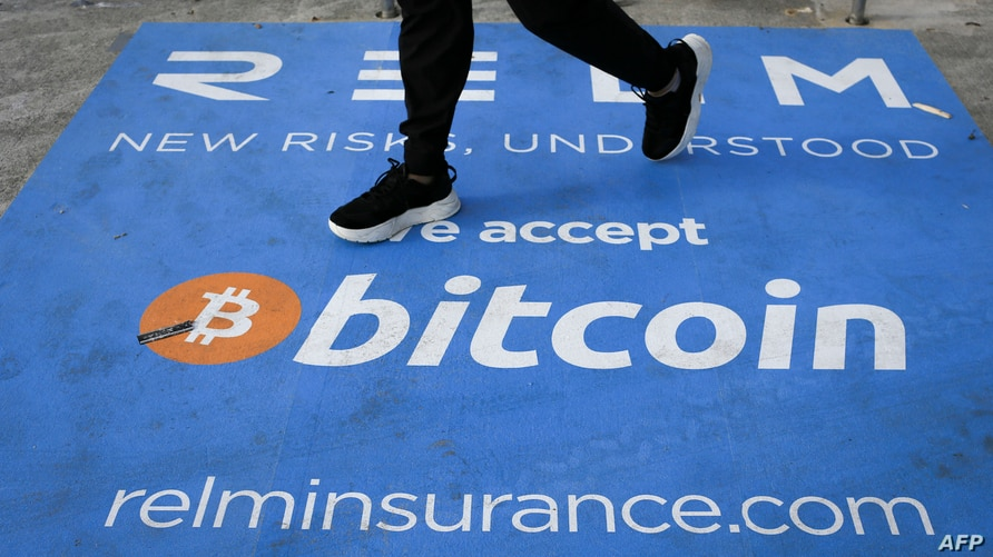 (FILES) In this file photo a man walks past a banner with the logo of bitcoin during the crypto-currency conference Bitcoin…