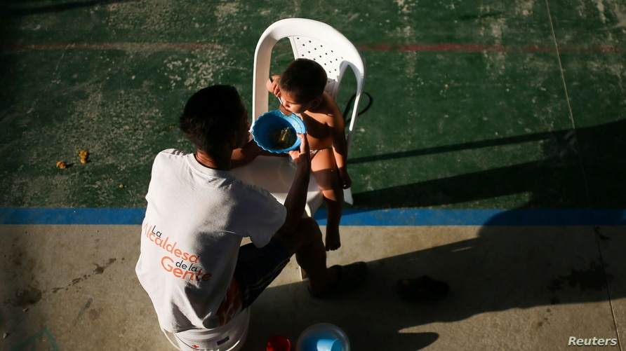 A Venezuelan migrant man feeds his son inside a coliseum where a temporary camp has been set up, after fleeing their country…