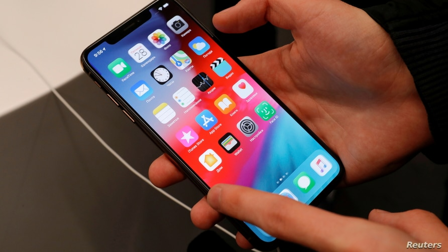 """FILE PHOTO: A customer tests a smartphone during the launch of the new iPhone XS and XS Max sales at """"re:Store"""" Apple reseller…"""