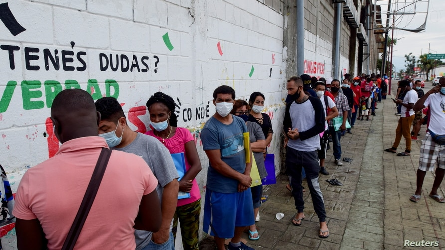 Migrants from Central America, Haiti and Cuba queue outside the Mexican Commission for Refugee Assistance (COMAR) to apply for…
