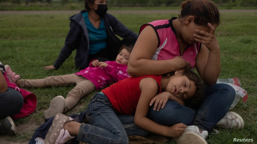 Claudia, an asylum-seeking migrant mother from Honduras,   holds her daughter Angelie, 5, as she awaits amid others families to…
