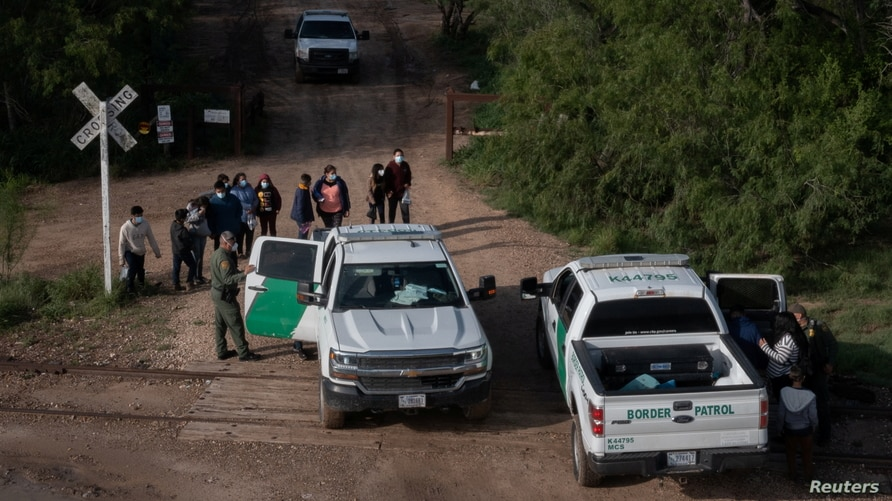 Asylum-seeking migrants from Central America are placed into U.S. board patrol vehicles after crossing the Rio Grande river…