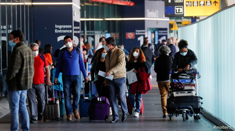 FILE PHOTO: Travellers walk with their luggage at Fiumicino Airport after Italy lifted quarantine restrictions for people…