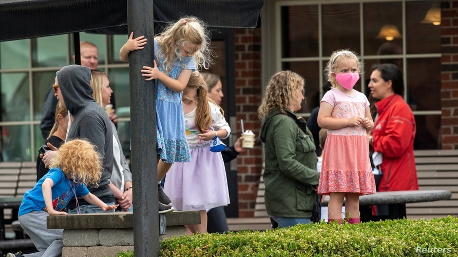 Kids wear face masks while adults remain unmasked at Johnson's Real Ice Cream as the coronavirus disease (COVID-19)…