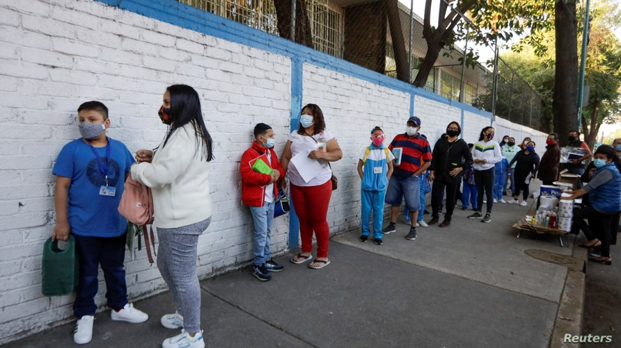 Parents and their children queue to enter the Ignacio Zaragoza elementary school as Mexico City's authorities resumed in-person…