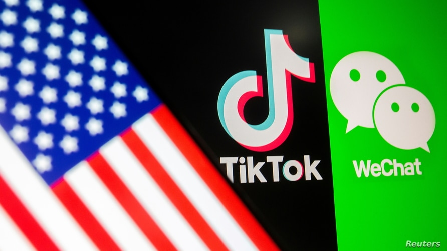 FILE PHOTO: A U.S. flag is seen on a smartphone in front of displayed Tik Tok and WeChat logos in this illustration taken…