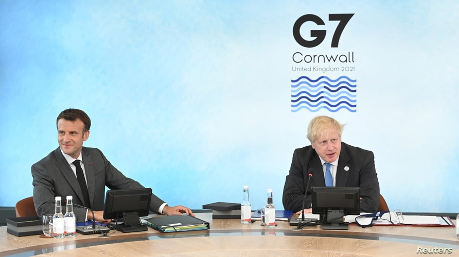 British Prime Minister Boris Johnson and French President Emmanuel Macron, sit around the table at the top of the G7 meeting in…