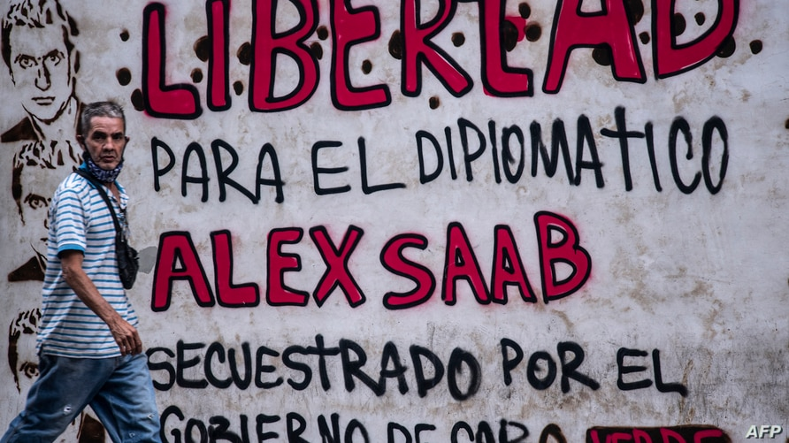 """A man walks past a graffiti reading """"Freedom for diplomat Alex Saab, kidnapped by the government of Cape Verde"""" in Caracas, on…"""