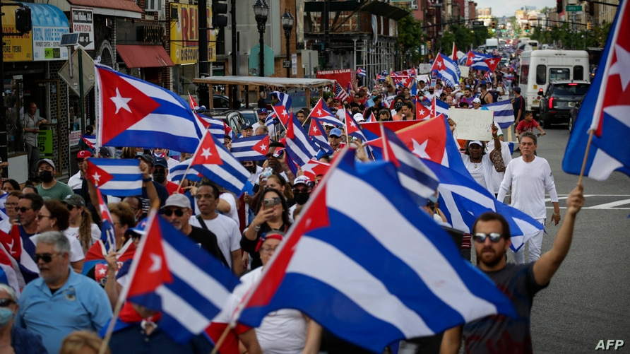 People wave Cuban flags as they march during a protest showing support for Cubans demonstrating against their government, in…