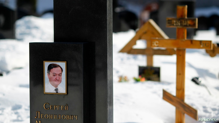 A picture of lawyer Sergei Magnitsky is seen on his grave in the Preobrazhensky cemetery in Moscow March 11, 2013. A Russian…