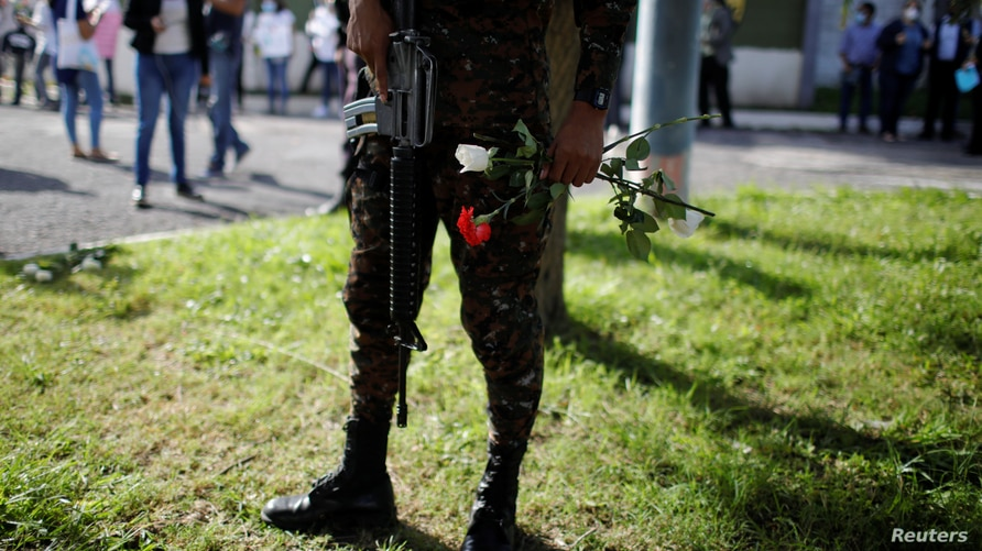 A soldier holds flowers given by protestors outside the installations of El Salvador's Air Force as the military rejected a…