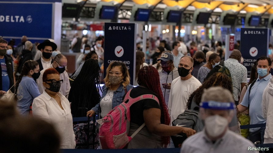 FILE PHOTO: Passengers gather near Delta airline's counter as they check-in their luggage at Hartsfield-Jackson Atlanta…