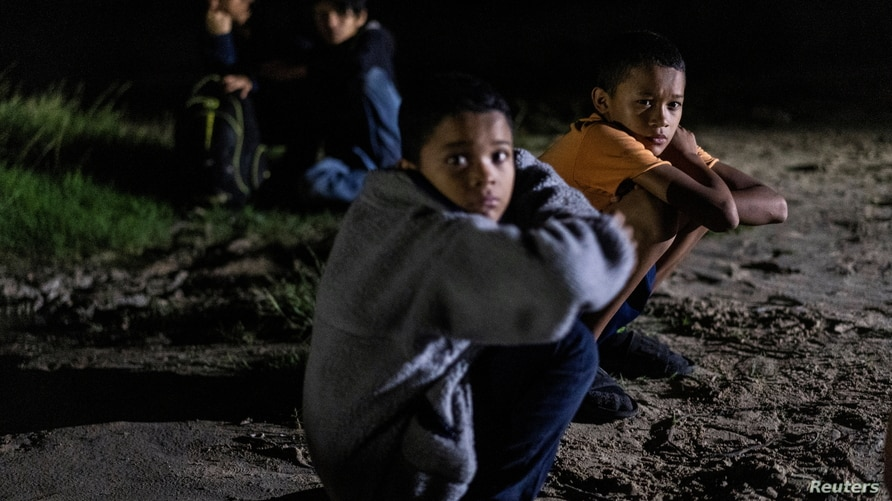 Unaccompanied minor migrants from Honduras Alejandro, 10, and his brother Cristopher, 12, sit at the riverbank as they wait to…