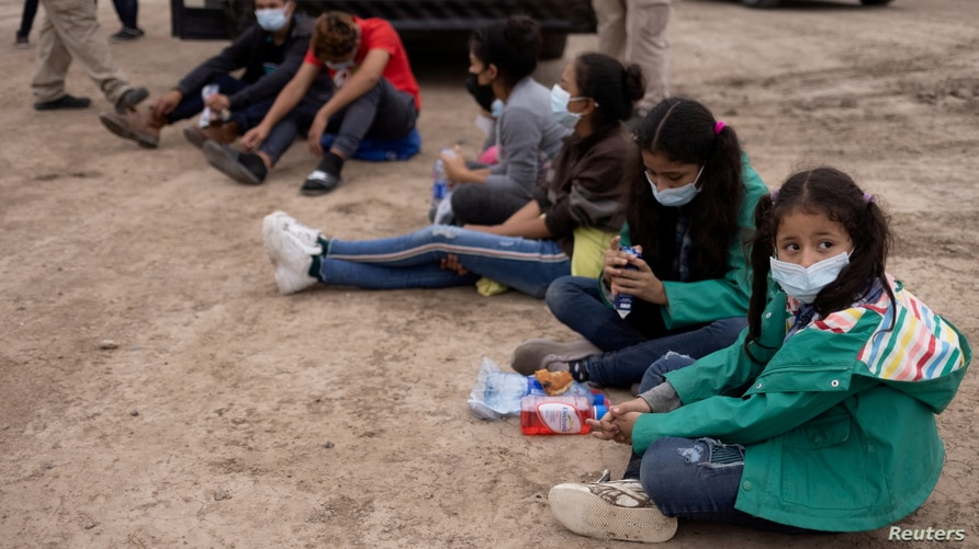 FILE PHOTO: Chanel, 7, and her sister Adriana, 10, both unaccompanied minors traveling alone from Honduras, sit among other…