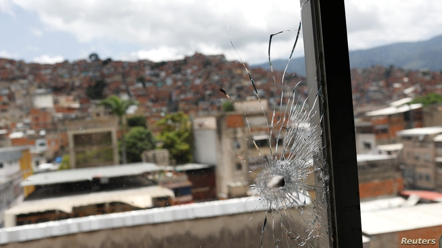 A window hit by a bullet is seen in the offices of the San Miguel Archangel church after armed confrontations between members…