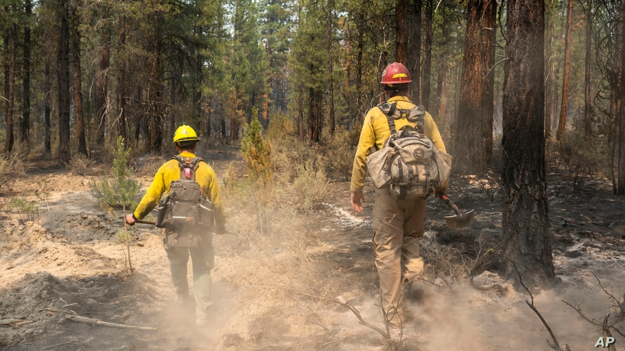 Firefighters Garret Suza, right, and Cameron Taylor, with the Chiloquin Forest Service, search for hot spots on the North East…