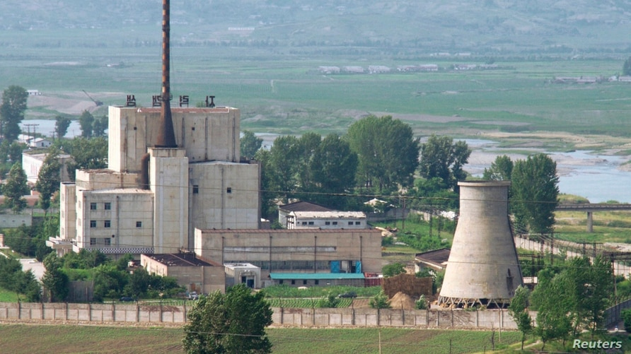 A North Korean nuclear plant is seen before demolishing a cooling tower (R) in Yongbyon, in this photo taken June 27, 2008 and…