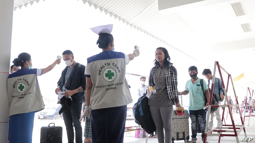 People have their temperatures checked amid concerns over the spread of the COVID-19 coronavirus at the immigration post in…