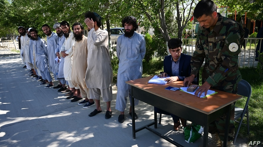 Afghan National army solders (ANA) register Taliban prisoners during thier release from the Bagram prison, next to the US…