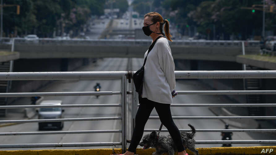 A woman wearing a face mask walks her dog at Libertador Avenue in Caracas on May 14, 2020 amid the novel coronavirus (COVID-19)…