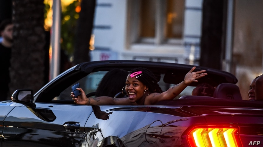 (FILES) In this file photo taken on June 26, 2020 a woman shouts as she drives thru Miami Beach, Florida. - Florida on June 27,…