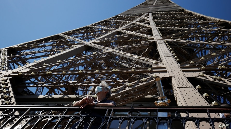 TOPSHOT - A visitor wearing a protective facemask admires the view from the Eiffel Tower during its partial reopening on June…