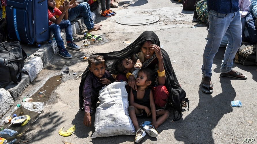 TOPSHOT - A woman covers her children with a shawl to protect them from the sun as she waits with other migrant workers and…