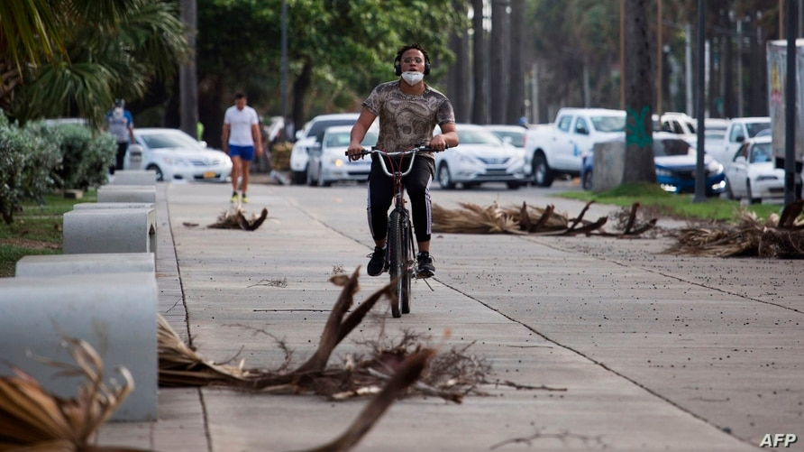 A cyclist rides along the seafront in Santo Domingo on July 29, 2020. - Dominican Republic's Emergency Operation Center (COE)…