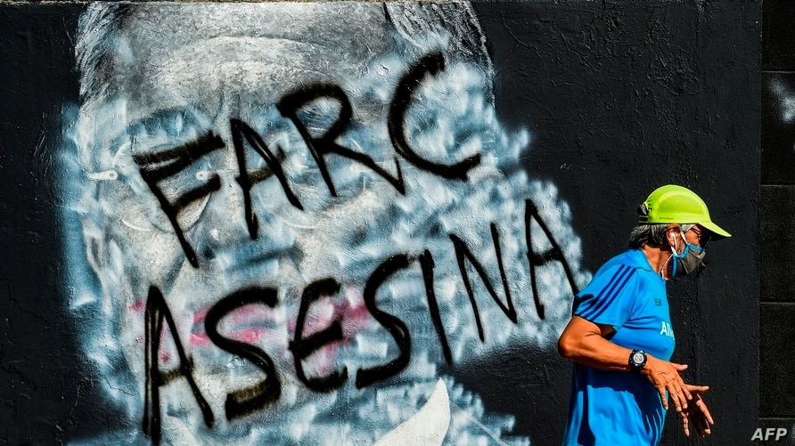 A man jogs past a mural against former Colombian President (2002-2010) Alvaro Uribe, which was painted over and now shows a…