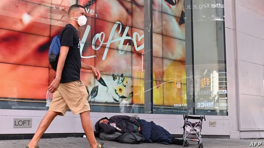 A homeless person sleeps in front of a store at Time Square on September 28, 2020 in New York City. - Coronavirus infection…