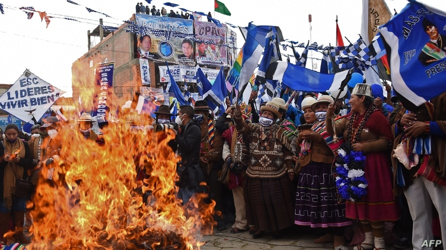 TOPSHOT - Supporters of Bolivian leftist presidential candidate Luis Arce surround a bonfire during the closing rally of his…