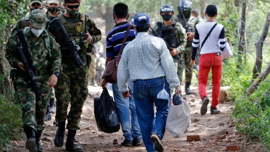 """Colombian Military Police officers and soldiers stand guard at the """"trochas"""" -illegal trails on the border between Colombia and…"""