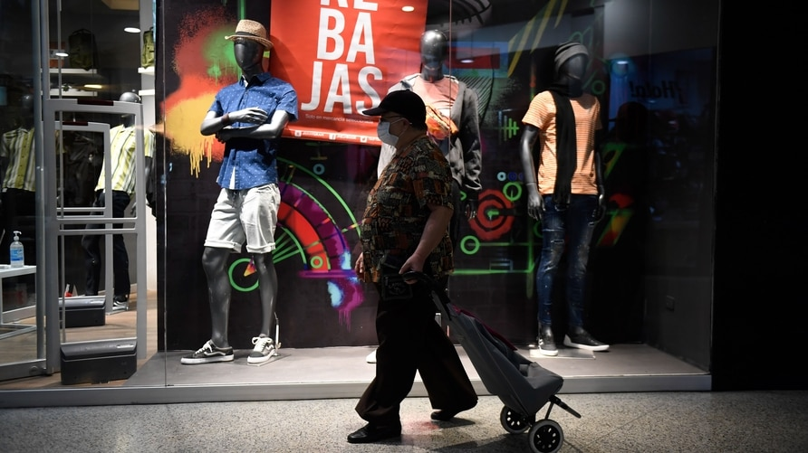 A man walks past a store window advertising Black Friday discounts at a shopping centre in Caracas, Venezuela on November 20,…