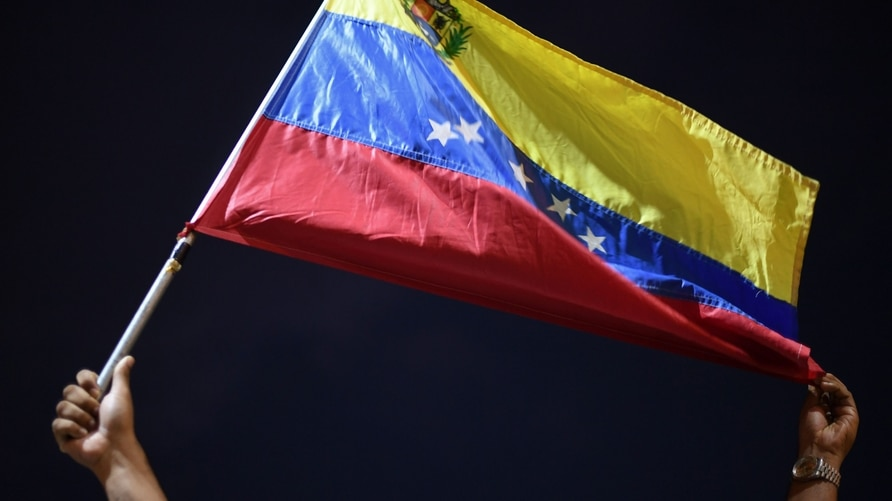 A man displays a Venezuelan flag as relatives and friends of 28 Venezuelan migrants who died when a boat transporting them to…