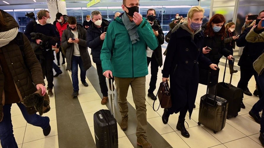 Russian opposition leader Alexei Navalny and his wife Yulia walk towards the passport control point at Moscow's Sheremetyevo…