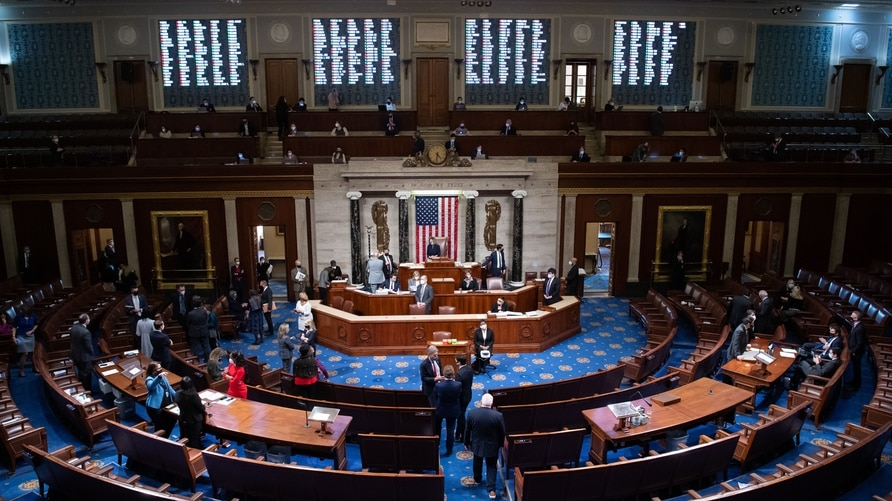 Speaker of the House Nancy Pelosi (C) presides over the House of Representatives as they conclude the vote to impeach US…