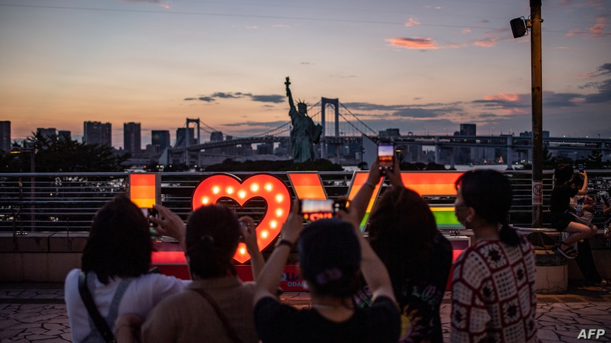 People take pictures of a replica Statue of Liberty at Odaiba waterfront in Tokyo on July 22, 2021, on the eve of the start of…