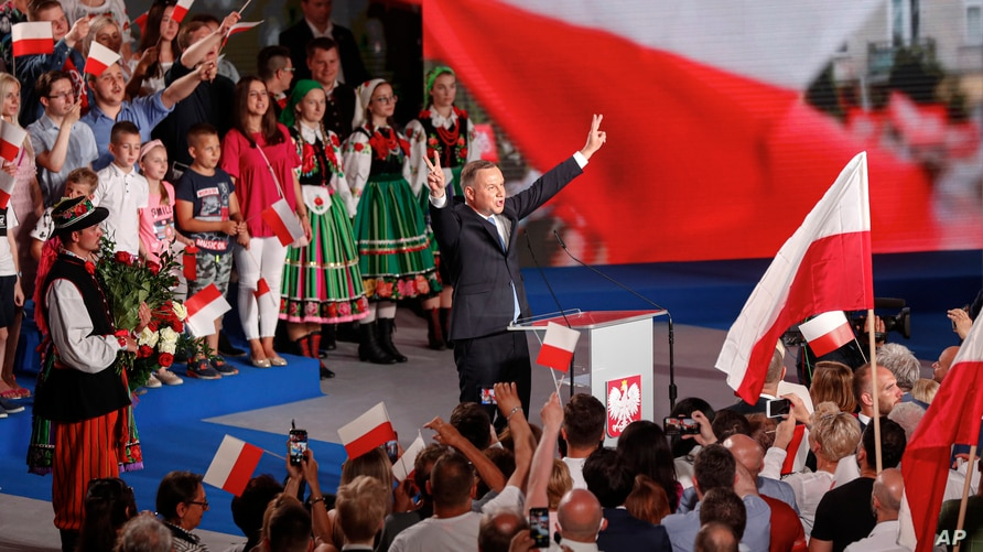 President Andrzej Duda flashes victory signs after voting ended in the presidential election in Lowicz, Poland, Sunday, June 28…