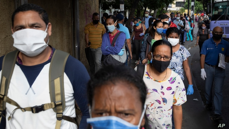 People wearing protective face masks as a measure to help curb the spread of the new coronavirus, walk near a bus stop in…